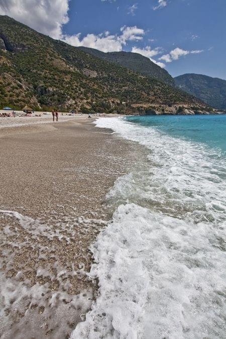 Turcja. Zdjęcie zrobione na plaży w lagunie Oludeniz. Podobno jest to najpiękniejsza plaża całej Turcji Egejskiej. Woda ma tu niesamowity lazurowy kolor. Nad głowami plażowiczów przelatują paralotniarze, oglądający z góry te niesamowite widoki.